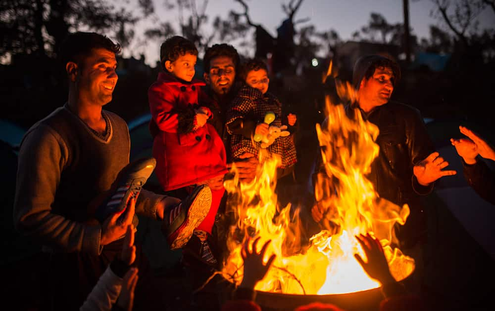 Members of several Afghan families try to warm up next to a bonfire outside a processing center in Moria village on the northeastern Greek island of Lesbos.