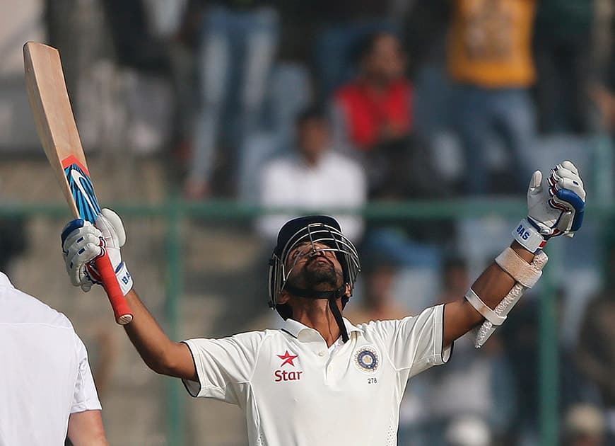Ajinkya Rahane raises his bat and looks heavenwards after scoring a century against South Africa, on the second day of the fourth test match between the two countries, in New Delhi.