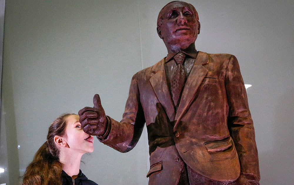A girl tries to lick a chocolate statue of Russian President Vladimir Putin during the Chocolate Festival in St.Petersburg, Russia.