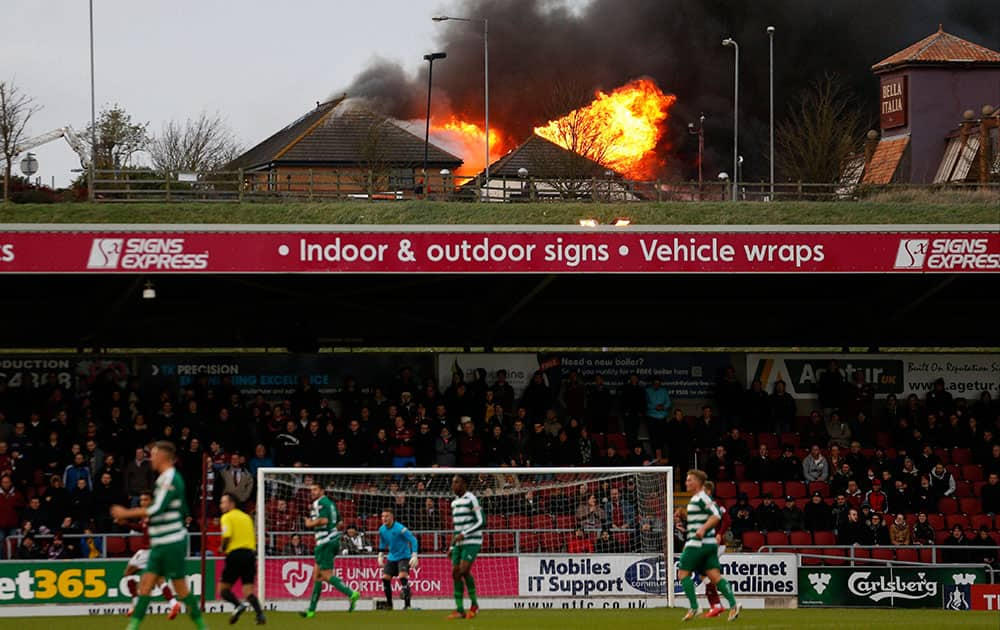 Fire rages at the near by Sixfields Tavern as play continues during the FA Cup second round match between Northampton and Norwich Victoria at Sixfields Stadium, Northampton, central England.