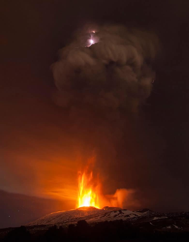 Lightning flashes inside a plume of smoke during an eruption of Mt. Etna near Catania, Italy.