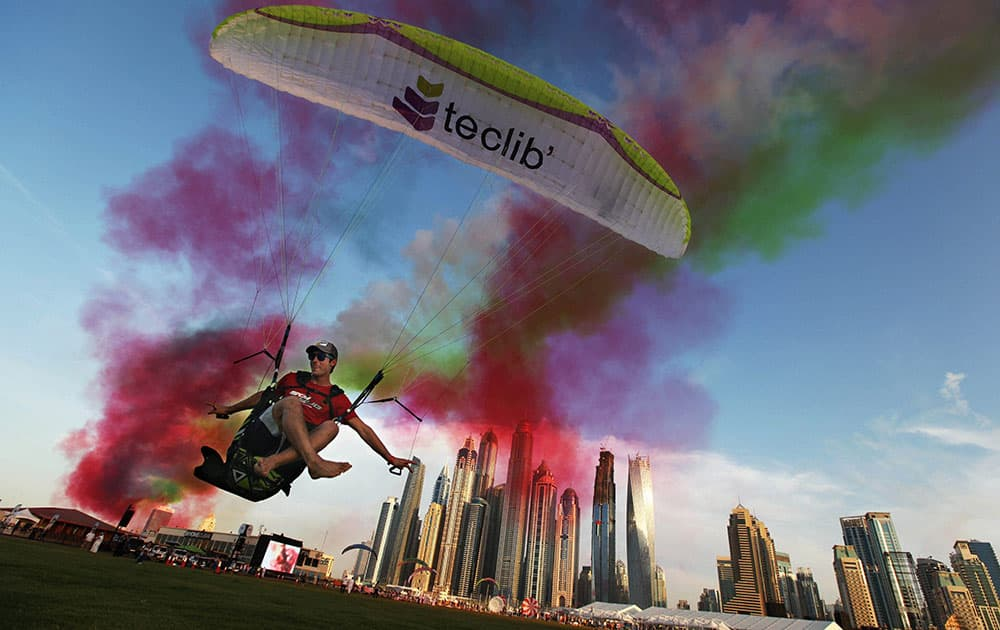 Paraguilder Ragolski Francois, 28, of France takes a practice run and leap just after an aerobatic team raced by at the World Air Games in Dubai.