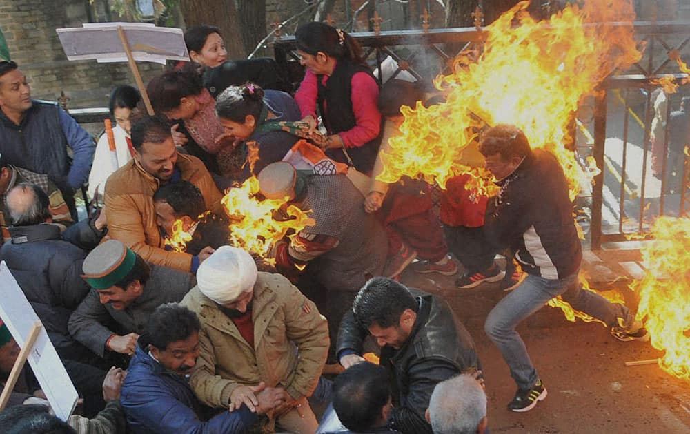 Activists of Congress party try to flee after their clothes caught fire while they were trying to burn an effigy of Prime Minister Narendra Modi during a protest in Shimla.