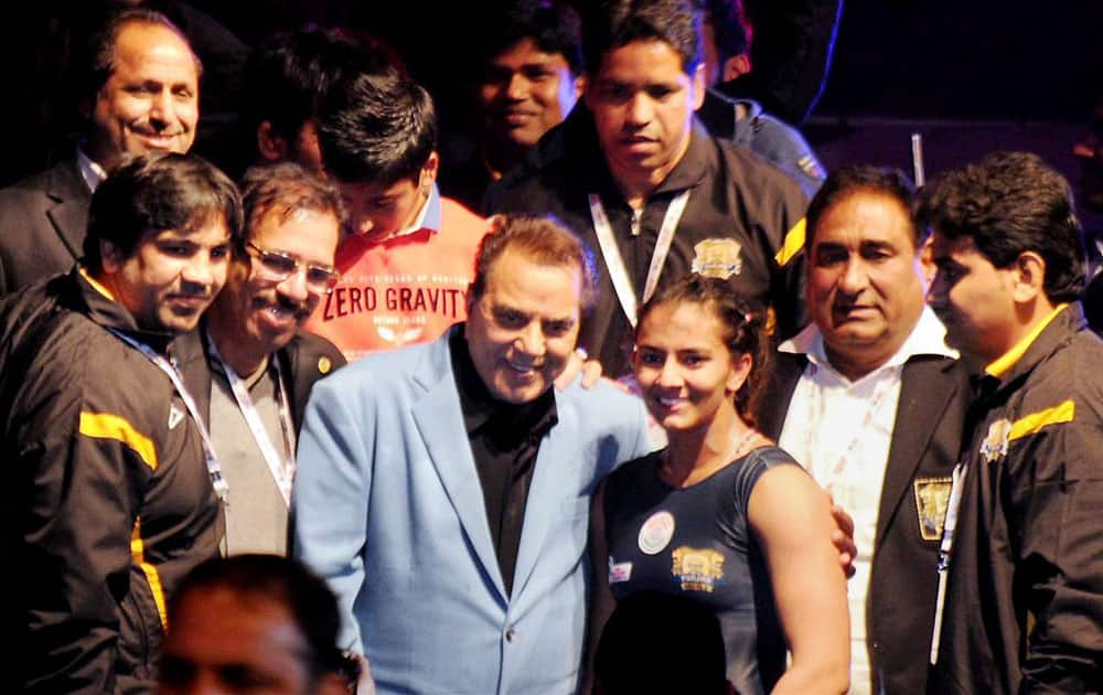 Actor Dhramendra poses for photographs along with wrestlers during the Pro-wrestling League in Ludhiana.
