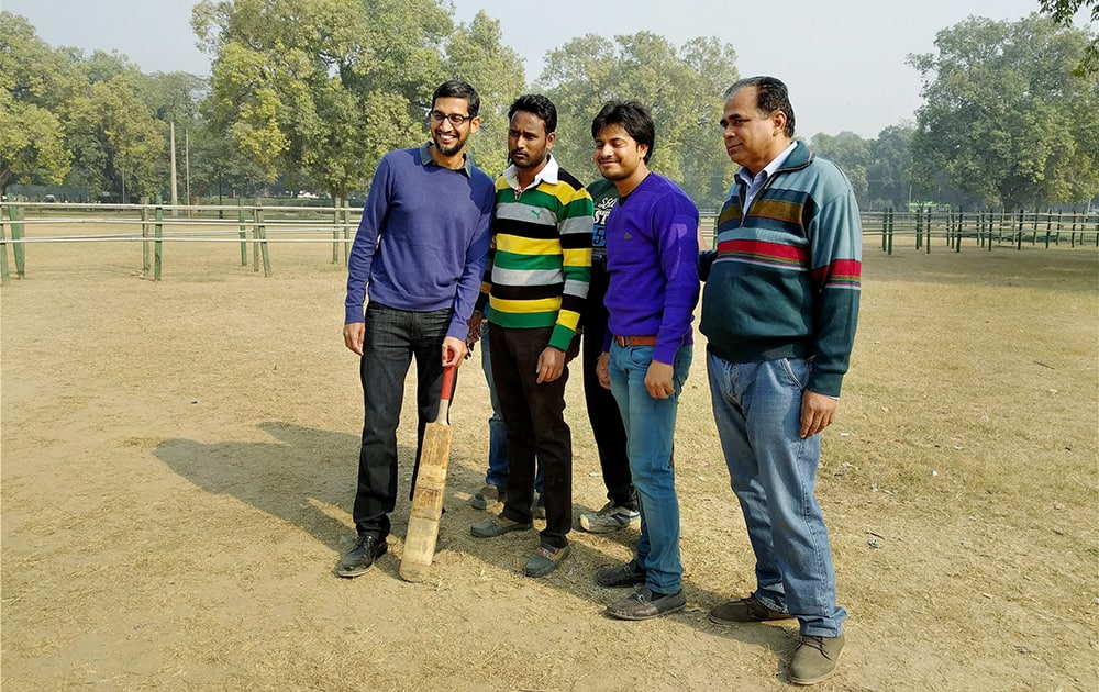 CEO of Google, Sundar Pichai (L) poses for photograph with the local people after playing cricket with them at India Gate in New Delhi.