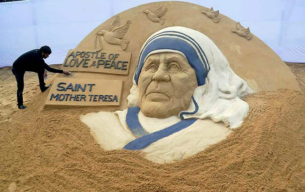 Sand Artist Sudarsan Pattnaik creates a sand sculpture of Mother Teresa with the message Apostle of Love & Peace Saint Teresa at Rourkela Steel City in Sundargarh district on Friday. Mother Teresa will be made a Saint of Roman Catholic Church the next year.