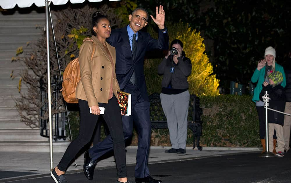 President Barack Obama waves as he and his daughter Sasha walk from the White House to board Marine One, in Washington, for the short trip to Andrews Air Force Base en route to San Bernardino, Calif.