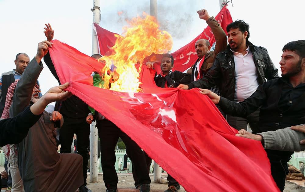 Protesters burn a Turkish flag during a demonstration calling for the withdrawal of Turkish troops from northern Iraq, in Basra.