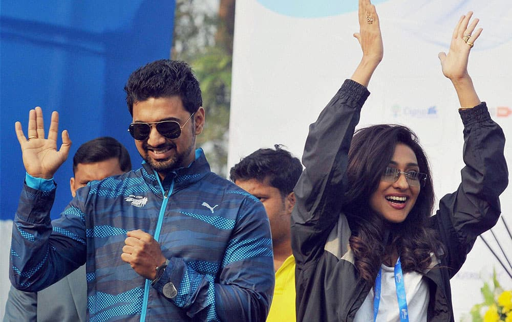Actor and Trinamool Congress MP Dev with actress Rituparna Sengupta gesture to the participants of Tata Steel Kolkata 25k run, at Red Road in Kolkata.