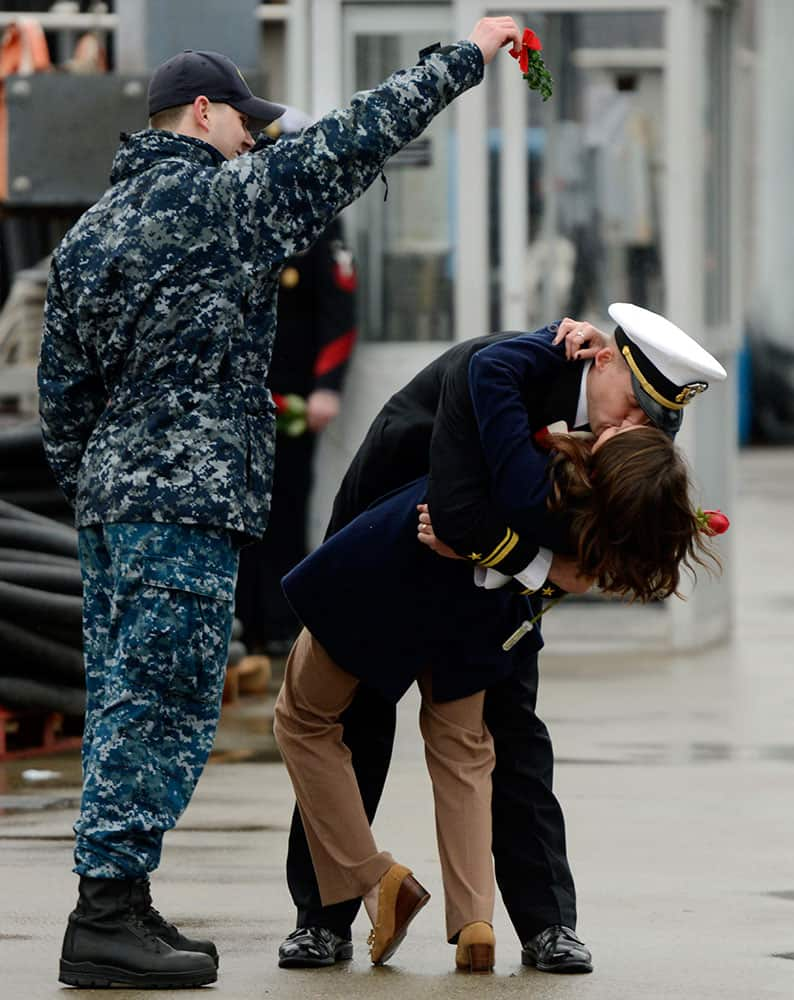 U.S. Navy Lt. jg. Stephen Bogdanowicz, left, holds a sprig of mistletoe as Ensign Morgan Oblinsky and his wife Katie enjoy the ceremonial first kiss as the navy attack submarine USS Hartford returns to the U.S. Navy Submarine Base in Groton, Conn.