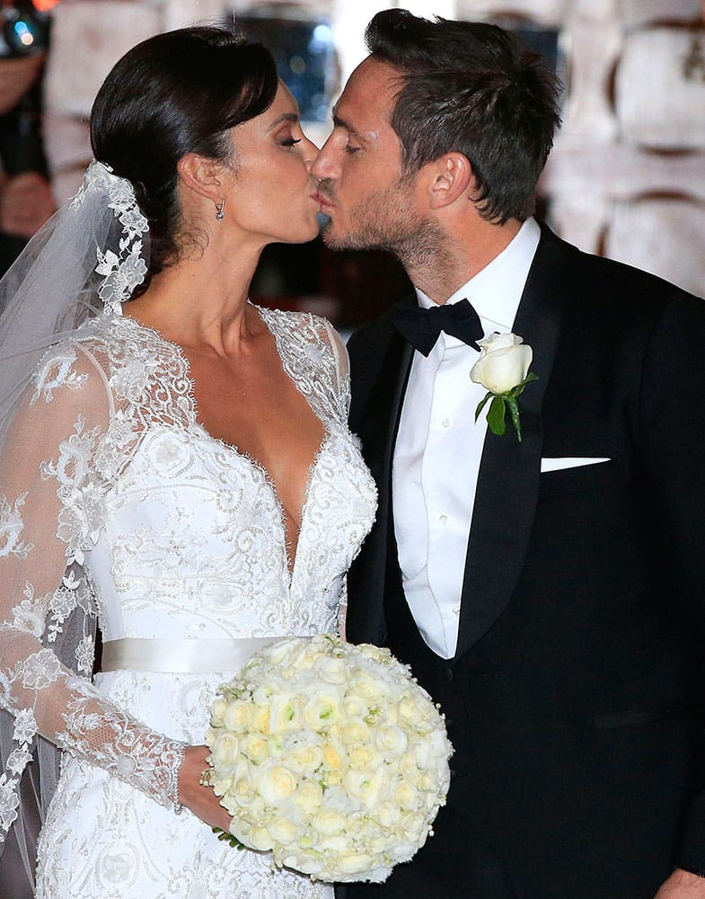 British TV personality Christine Bleakley, left, kisses British soccer player Frank Lampard as they leave after their wedding, at St Paul's Church, in Knightsbridge, London.