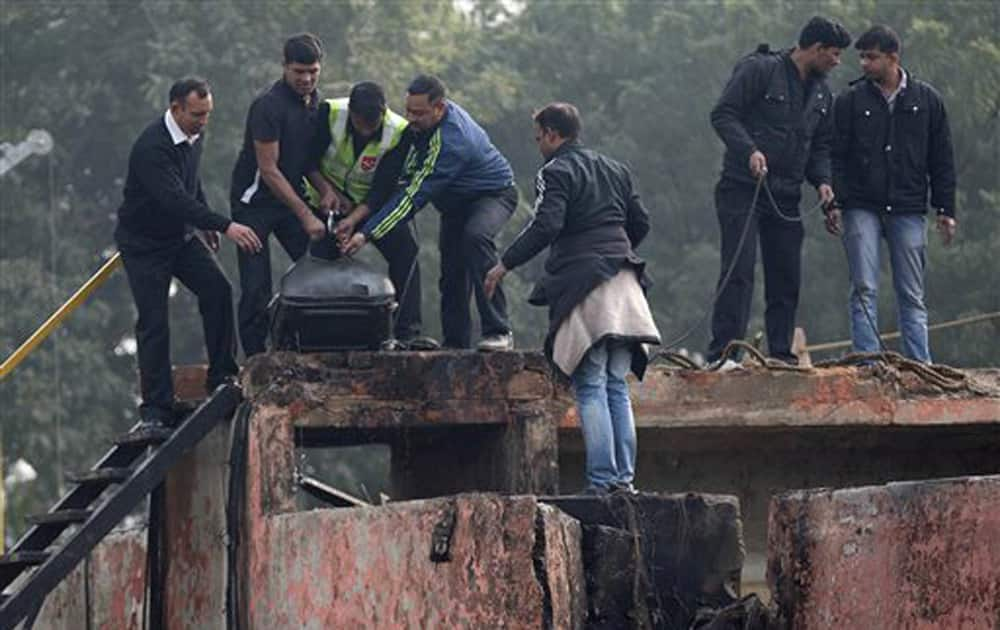 Indian security personnel stand near a destroyed boundary wall after a small Indian paramilitary plane crashed outside the main airport in New Delhi, Dec 22, 2015.