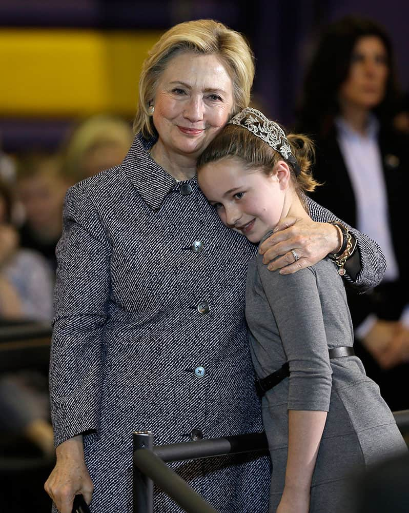 Democratic presidential candidate Hillary Clinton gets a hug from fifth-grader Hannah Tandy during a town hall meeting at Keota High School in Keota, Iowa.