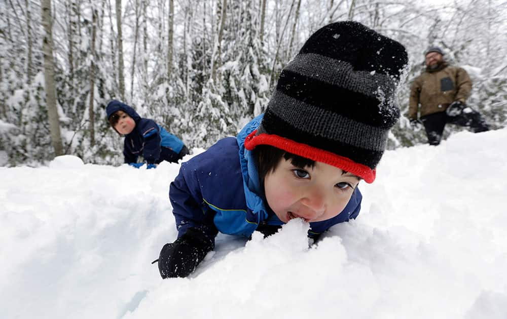Leon Perkins, 3, leans forward to take a bite of snow as he plays with his brother Conner, left, 2, and his father Erin at Snoqualmie Pass, Wash.