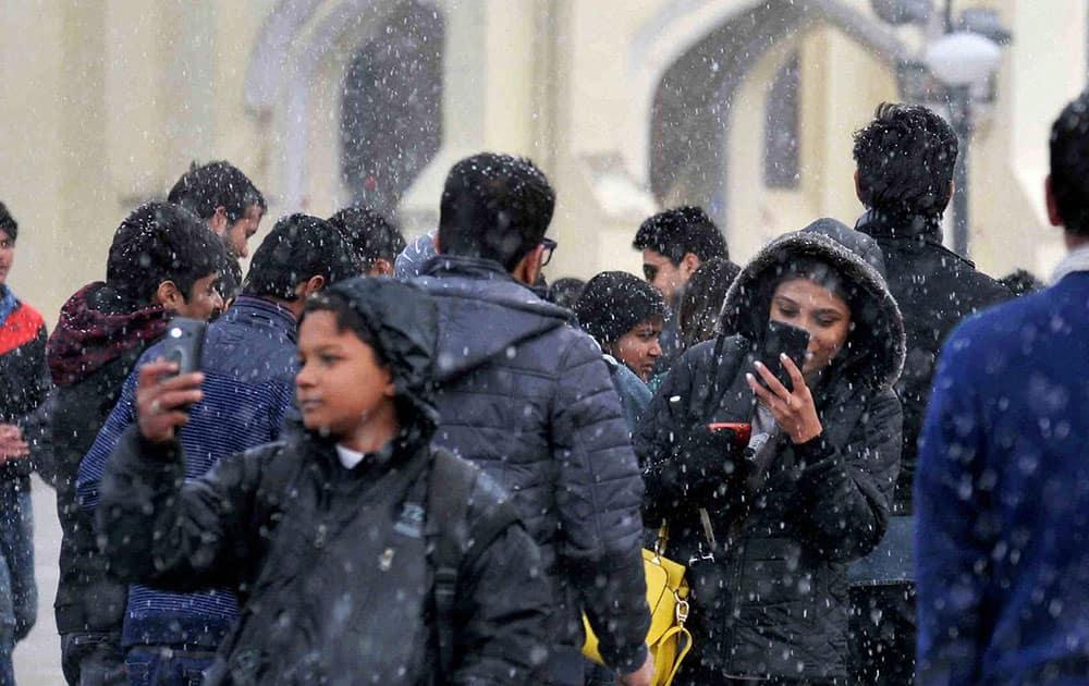 People enjoy the snowfall in Shimla.
