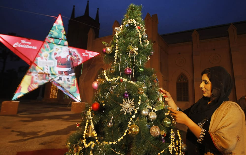 A PAKISTANI WOMAN DECORATES A CHRISTMAS TREE FOR THE UPCOMING CHRISTMAS HOLIDAY IN PESHAWAR, PAKISTAN.