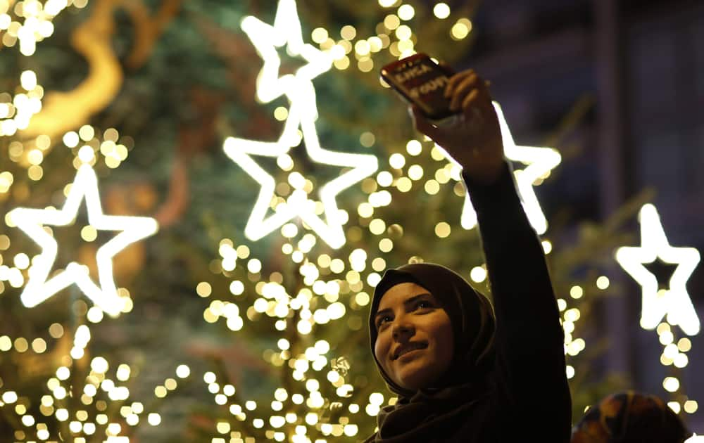 A Muslim Lebanese woman takes a selfie with Christmas trees in Downtown Beirut, Lebanon.