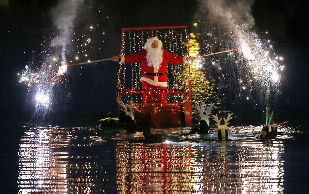 A man dressed as Santa Claus lights flares as he sits on a boat toed by swimmers, in Imperia, near Genoa, Italy.