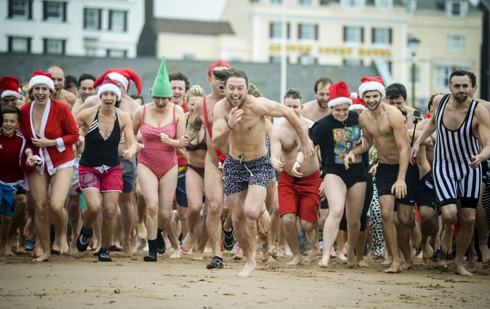 People take part in the annual Exmouth Christmas day swim, at Exmouth beach, in Devon, England.