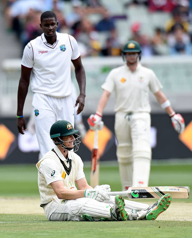 West Indies' Jason Holder, left watches on as Australia's Adam Voges lies on the ground after completing a run during their cricket test match in Melbourne, Australia.