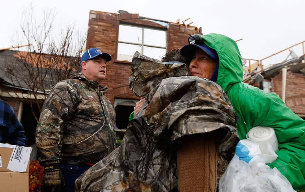 Cheryl Turek, of Nevada, Texas, right, hugs Evelyn Lindstrom in front of Lindstrom's destroyed home in Copeville, Texas, after heavy rain, high winds and tornados swept through North Texas.