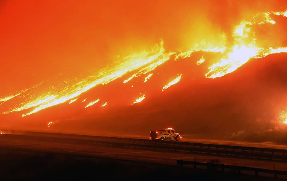 a Ventura County Fire Department engine holds its positions as fire overruns state Highway 101 near Ventura, Calif.