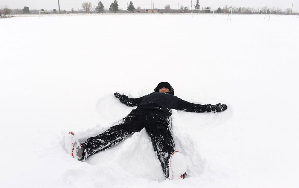 Brandon Dominguez makes a snow angel at McKinney Park in Odessa, Texas.