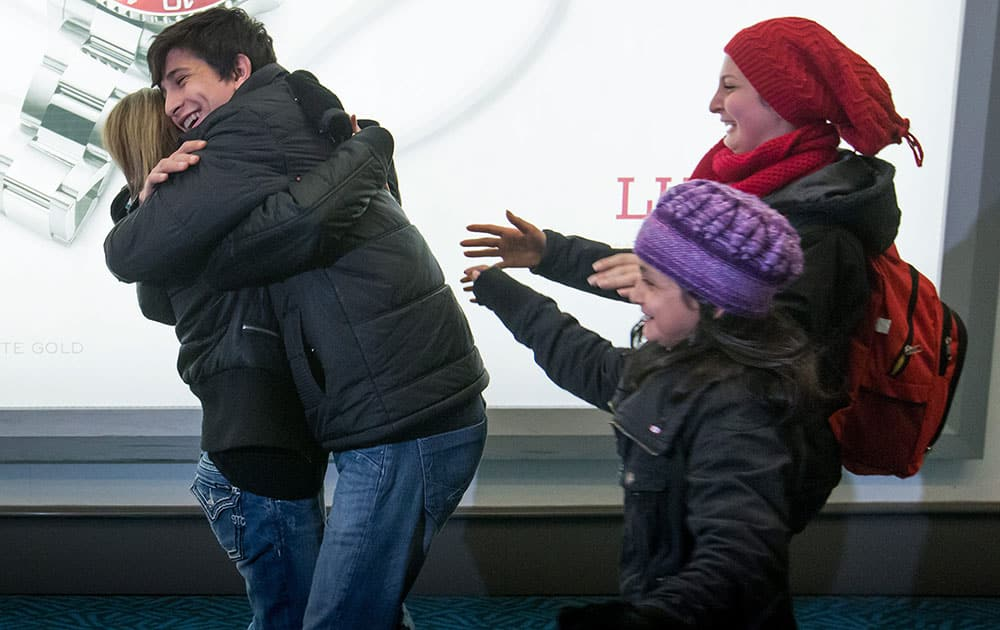 Shergo Kurdi, second from left, hugs his aunt, Tima Kurdi who lives in the Vancouver area, as his sisters Ranim Kurdi, front right, and Haveen Kurdi run to meet her after their family, who escaped conflict in Syria, arrived arrived at Vancouver International Airport, in Richmond, British Columbia.