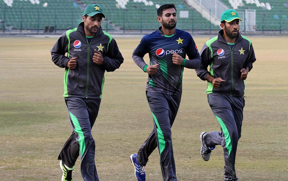 Pakistan fast bowler Mohammad Amir, left, runs with Shoaib Malik, center, and Shoaib Maqsood, right, during a training camp in Lahore, Pakistan.