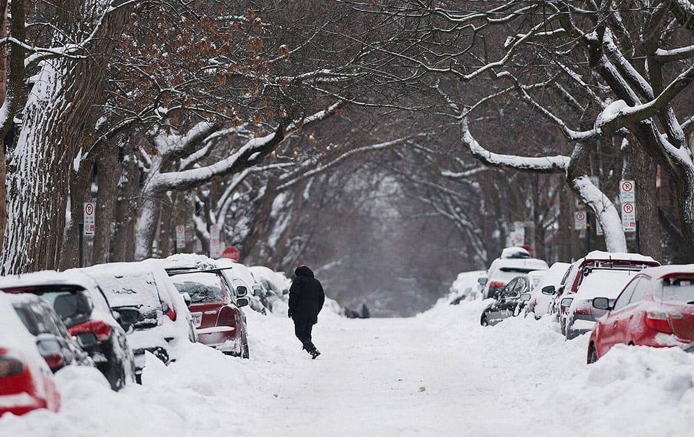 A man walks along a snow covered street in Montreal, following the first major storm of winter in the region.