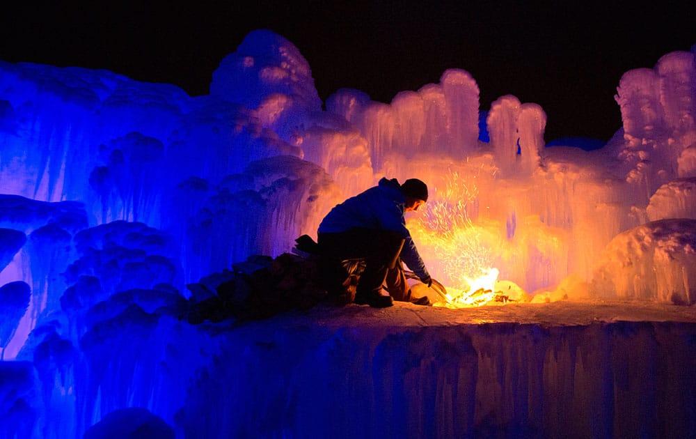 An employee stokes a fire in a giant ice castle in Edmonton, Alberta.