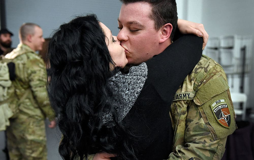 Sgt. Christopher Cruz of Danbury kisses his girlfriend, Amber Gerard, of Brewster, N.Y, after arriving at the National Guard's Windsor Locks Army Aviation Readiness Center in Windsor Locks, Conn.