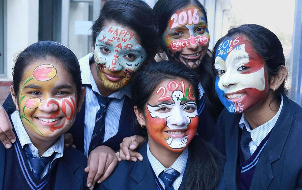School girls paint their faces with New Year greetings and wishes in Gurgaon.