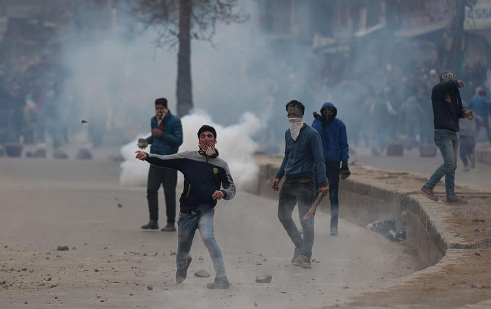 Kashmiri Muslim protesters throw stones at policemen during a protest in Srinagar.