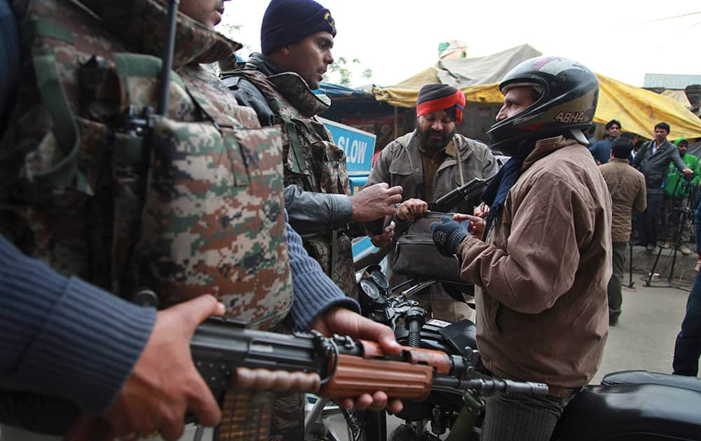 Indian security personnel check people entering an airbase in Pathankot.