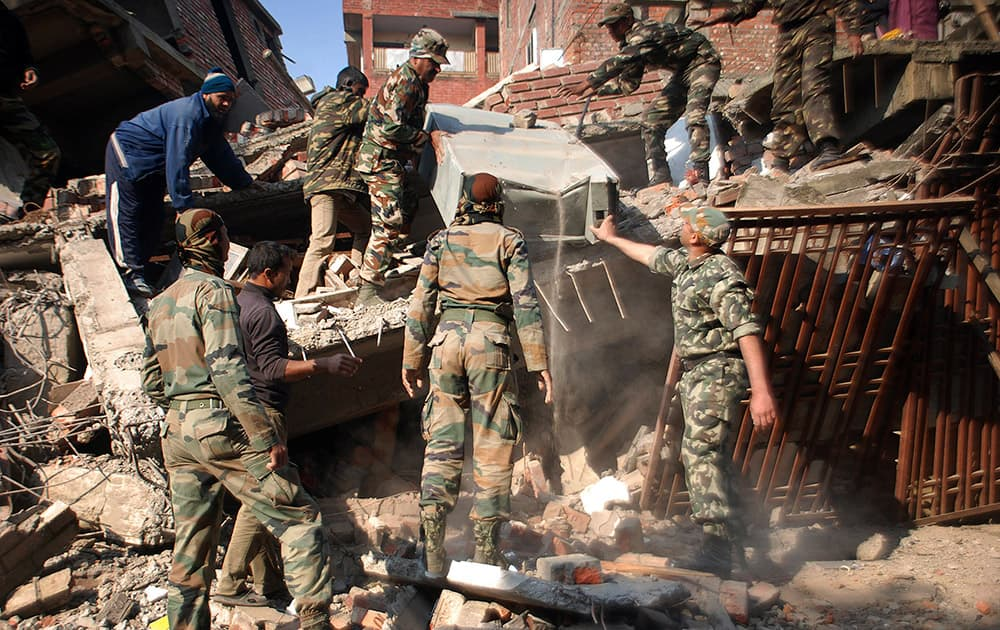 Indian soldiers remove debris from a damaged building after an earthquake in Imphal, Manipur. A 6.7 magnitude earthquake hit India's remote northeast region before dawn on Monday.