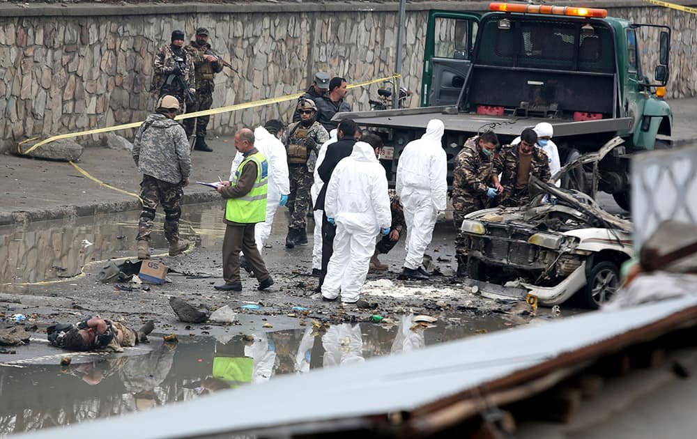 Afghan security forces inspect the site of a suicide attack near Kabul International Airport in Kabul, Afghanistan.
