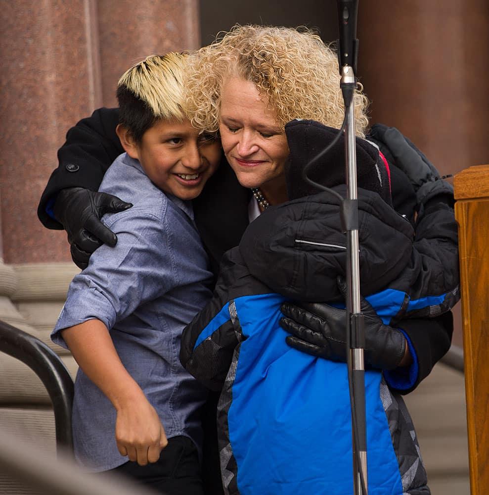 Jackie Biskupski hugs her sons Jack Iverson and Archie Biskupski following her remarks during a ceremony in Salt Lake City.