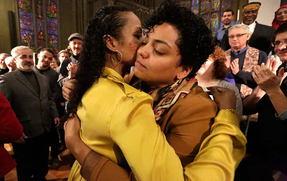Wheaton College professor Larycia Hawkins, left, is hugged by former student Rachel Brooks after a news conference in Chicago.