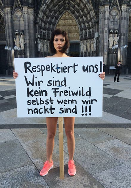 Swiss performance artist Milo Moire holds a sign Respect us! We are no fair game even when we are naked!!! as she protests naked in front of the Cologne, western Germany.