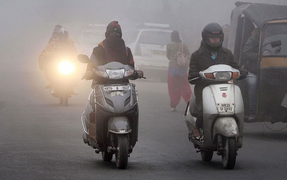 People don warm clothes and turned on the headlights of their vehicles as dense fog covered the better part of the day in Gurgaon.