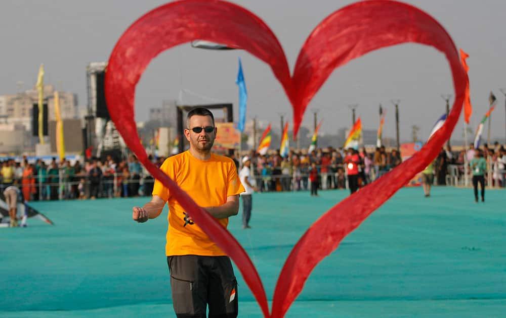A kite flyer from Switzerland flies his heart shaped kite during international kite festival in Ahmadabad.