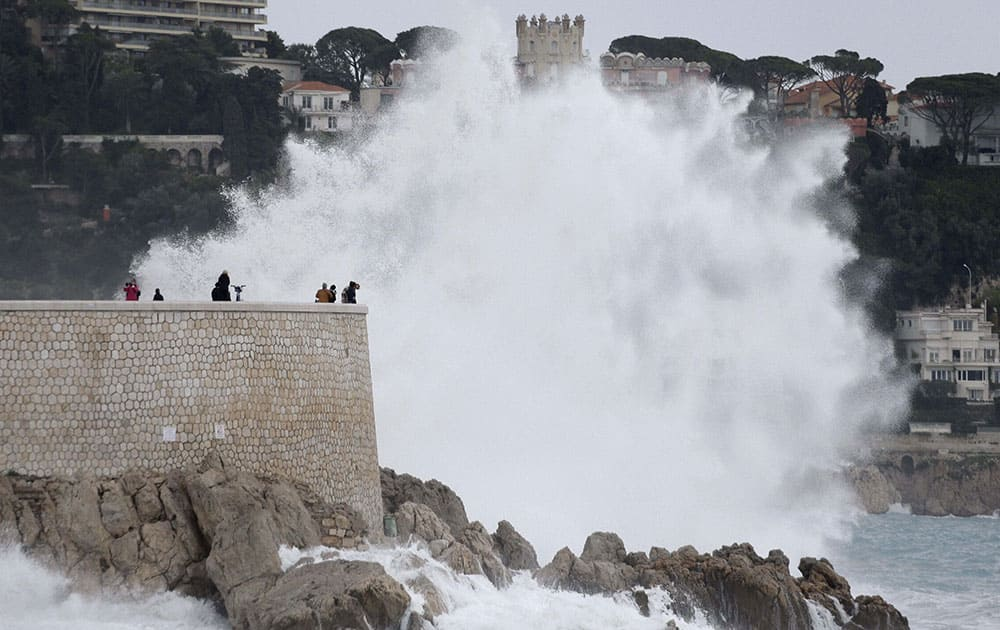 People look at a wave from Mediterranean sea in Nice, southeastern France during a high tide.