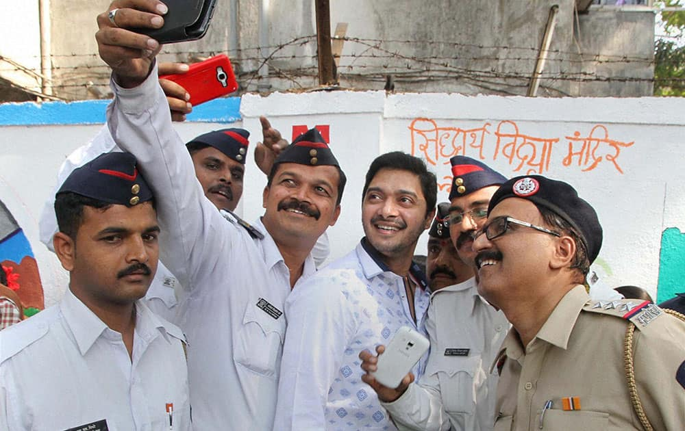 Bollywood actor Shreyas Talpade pose for a selfie with policemen as he takes part in a traffic awareness campaign during Road Safety Week in Thane, Mumbai.
