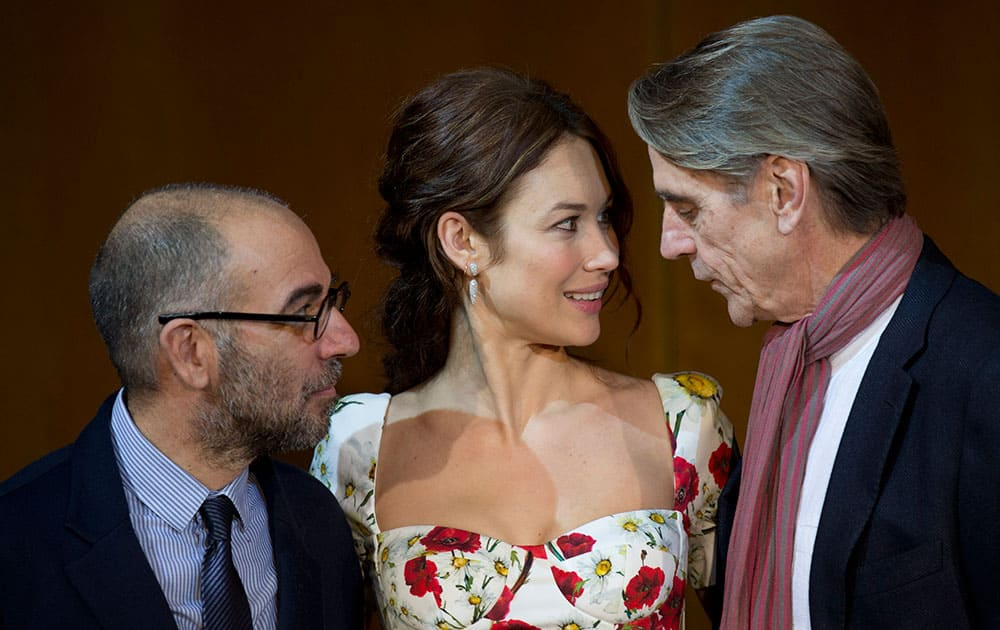 Actress Olga Kurylenko, center, is flanked by actor Jeremy Irons, right, and director Giuseppe Tornatore during the photo call of the movie La Corrispondenza in Rome.