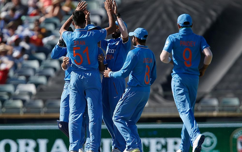 Barinder Sran is congratulated by teammates after taking a wicket during their one day international cricket match against Australia in Perth, Australia.