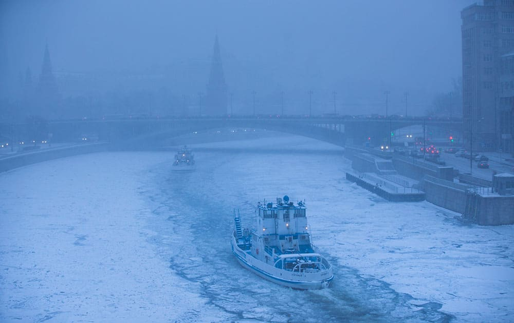 Two ice breakers move along the frozen Moskva River with the Kremlin in the background during snowfall in Moscow, Russia.