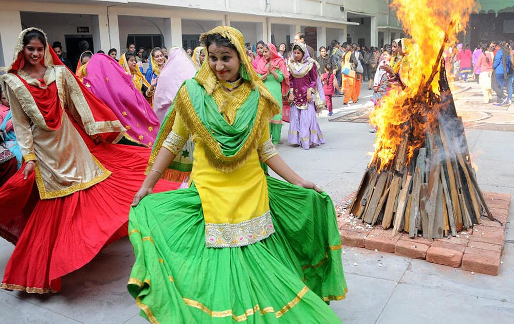 Attired in traditional dresses college girls perform gidha around a bonfire as they celebrate Lohri Festival in Amritsar.