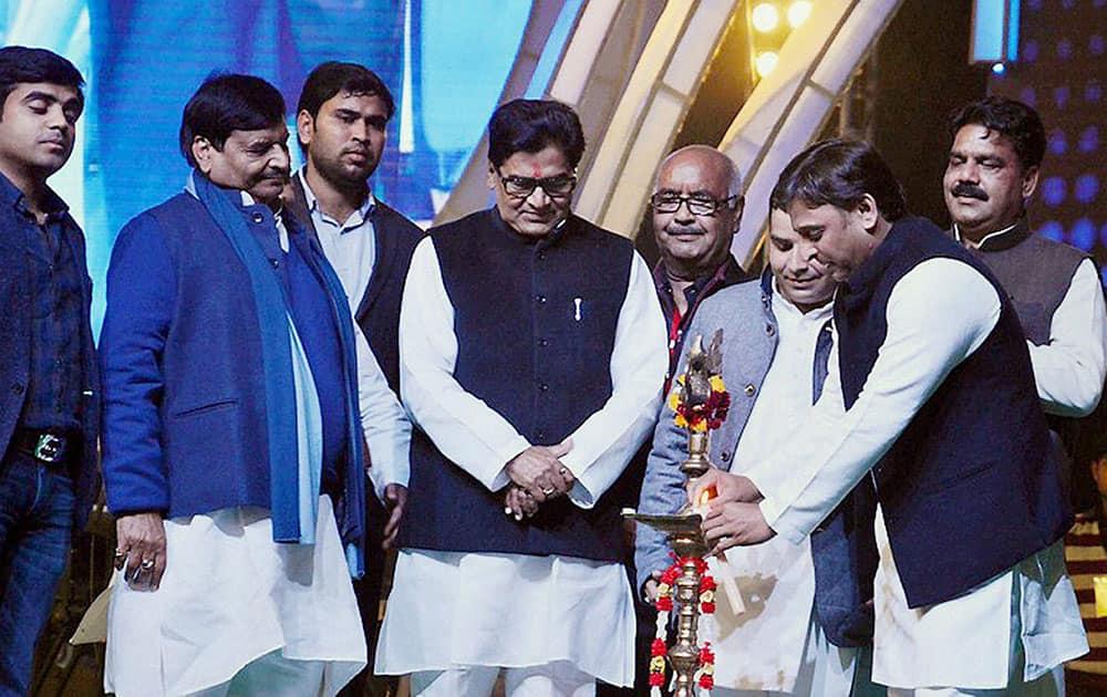 Chief Minister of Uttar Pradesh Akhilesh Yadav lighting lamps as MP Ram Gopal Yadav, Shivpal Singh Yadav and others look on during a cultural program at Saifai Mohotsav in Saifai.