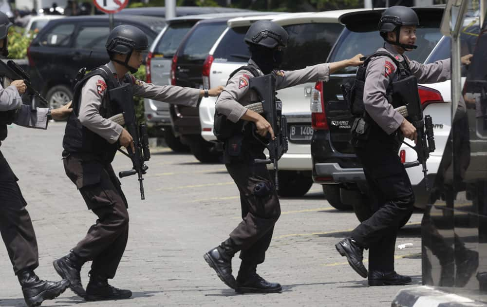 Police officers take their position near the site where an explosion went off in Jakarta.